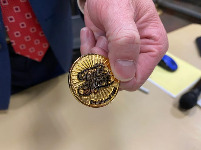 Adam Lenhard, St. George City Manager, holds a commemorative coin used to break a tied vote on February 10 deciding who would be appointed to fill Michele Randall's seat on the city council. Rick Erickson, a deputy Washington County attorney, won the coin toss.