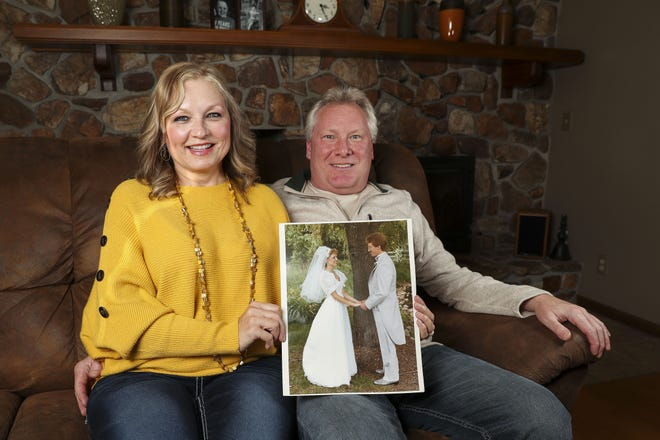 "Carol and Kurt Grasamkee hold up their wedding photo on Tuesday at their home in Plover. The couple will be featured on the ABC program ""LIVE with Kelly and Ryan"" on Thursday as part of a series about love stories leading up to Valentine's Day."