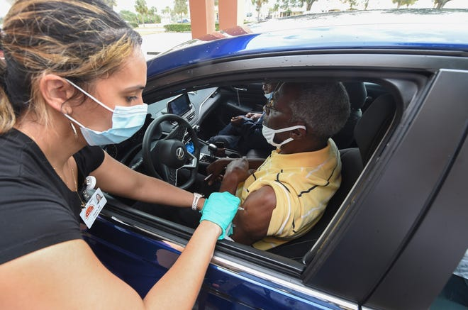 """Registered nurse Thalia Salis delivers the Pfizer/BioNTech COVID-19 vaccine to Gifford, Fla., resident Ricardo Hester during the Treasure Coast Community Health Center drive-in clinic for Indian River County residents age 65 or older on Saturday, Feb. 6, 2021, in Gifford. """"Great, glad I got it done. I need it, just like a lot of other people need it,"""" Hester said."""