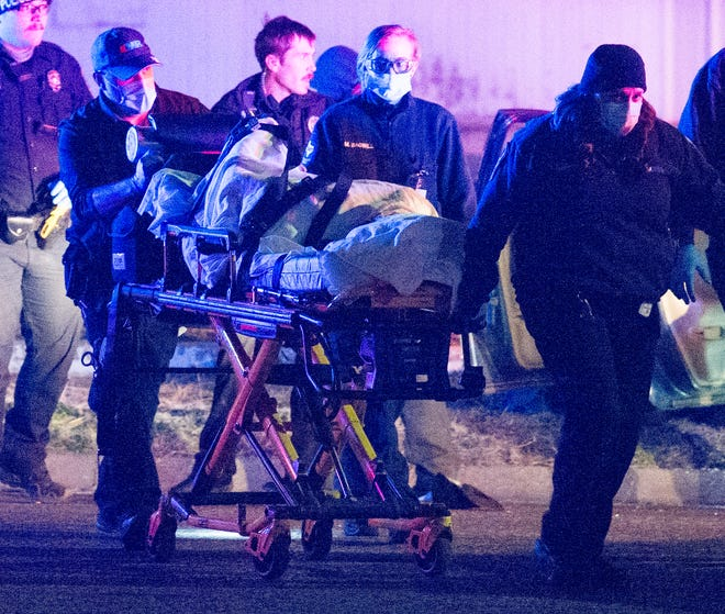 Wichita Falls emergency medics work to transport an alleged suspect that was involved in a pursuit Tuesday night after he crashed near Southwest Parkway at Maplewood.