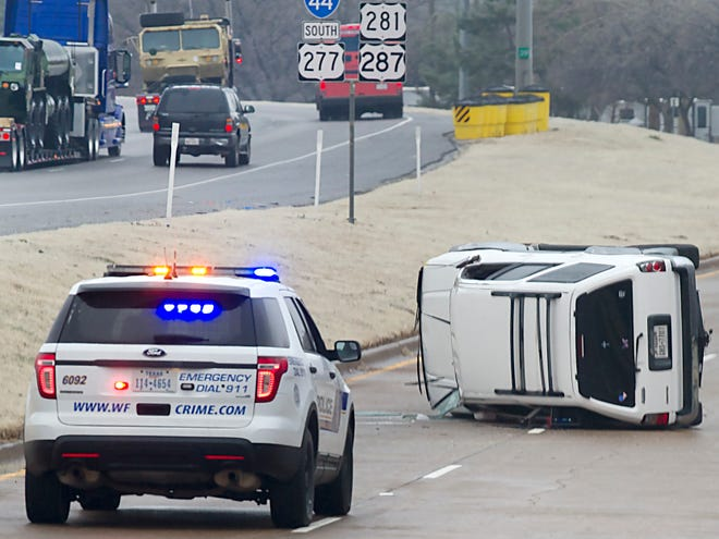 Wichita Falls Police work the scene of a wreck on Central Freeway early Wednesday. It was one of numerous accidents caused by freezing drizzle and slickened streets and highways.