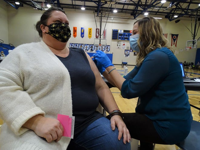 Ashlie Wilhite, an office secretary, smiles through the initial pinch of her Moderna shot in the Maysville High School gym on Wednesday, Feb. 10, 2020. Second doses are coming in four weeks on the dot.