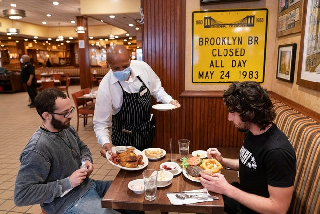 In this Sept. 30, 2020 file photo, Waiter Lenworth Thompson serves lunch to David Zennario, left, and Alex Ecklin at Junior's Restaurant in New York.