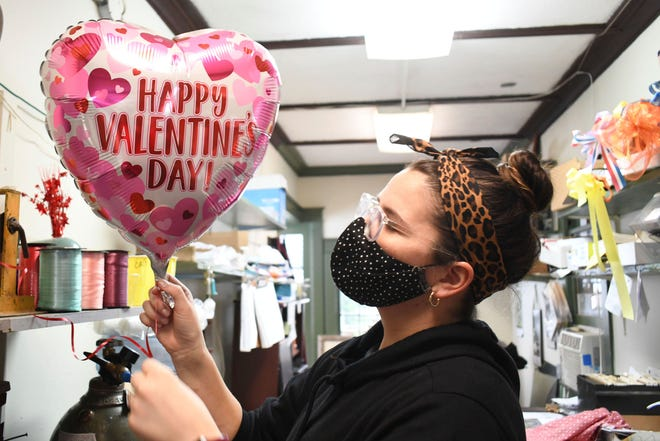 Carolyn Beaudreau wears a mask while blowing up a Valentine's Day balloon in North Adams, Mass on Feb. 9, 2021. Amid a pandemic, the holiday will be different than in years past.