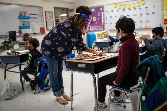 Teacher Elizabeth DeSantis, wearing a mask and face shield, helps a first grader during reading class at Stark Elementary School on September 16, 2020 in Stamford, Conn. Most students at Stamford Public Schools are taking part in a hybrid education model, where they attend in-school classes every other day and distance learn the rest. About 20 percent of students in the school district, however, are enrolled in the distance learning option due to coronavirus concerns.