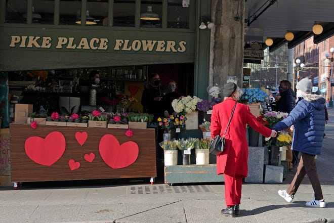 On Feb. 9, 2021, two people in masks hold hands in front of Pike Place Flowers in Seattle, which has been decorated for Valentine's Day.