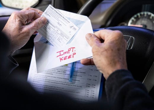 Jim Dixon pulls out his COVID-19 vaccination record card at Germantown Baptist Church in Germantown, Tenn., on Feb. 4, 2021.