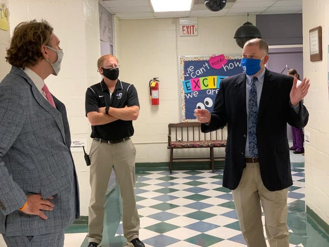 Patrick Miller, superintendent of Greene County Schools, right, speaks with Freebird McKinney, director of legislative and community affairs for the North Carolina State Board of Education, left, with Emery Smith, principal of Snow Hill Primary School.