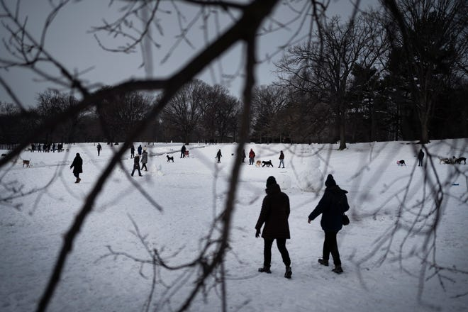 People gather on the snow-covered fields of the Long Meadow in Prospect Park to take a stroll at the start of the day Feb. 10, 2021, in the Brooklyn borough of New York.