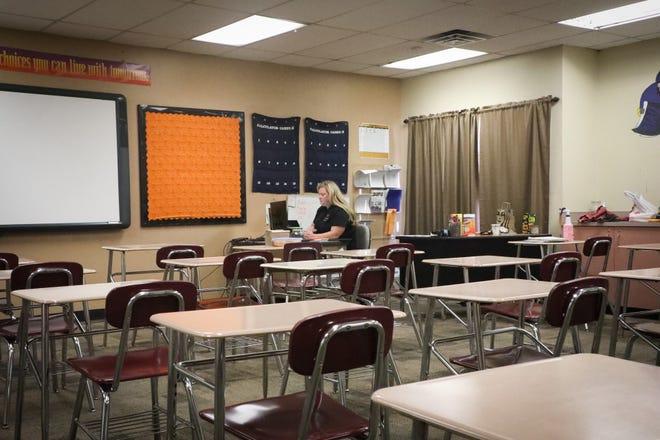 A math teacher at Trevor Browne High School in Phoenix teaching online in an empty classroom.