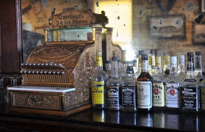 A vintage cash register and bottles of liquor at the Stonewall Saloon Museum in Saint Jo, Texas, hearken back to its original role as a rest stop for settlers and cowboys on the Chisholm Trail. The museum features a wide variety of historical artifacts from the early days of Montague County.
