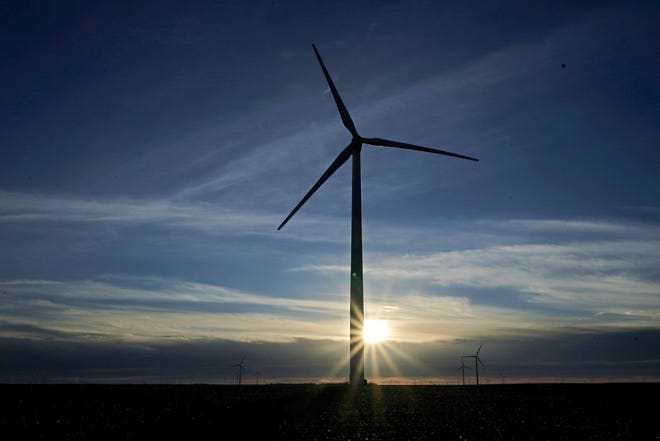 A wind turbine is silhouetted against the rising sun Jan. 13, near Spearville, Kan. [AP Photo/Charlie Riedel]