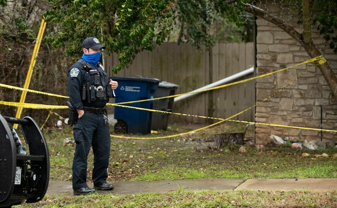 An Austin police officer guards a house on Rogge Lane on Thursday February 11, 2021, the day after police shot and killed a man who is accused of holding a woman and a child hostage.