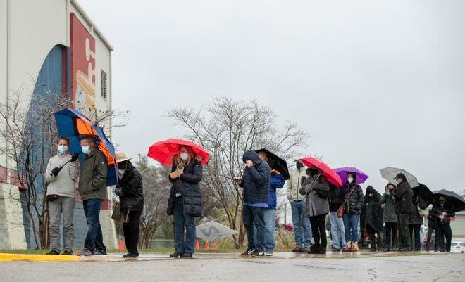 People wait in the cold rain for a COVID-19 vaccinations Thursday outside the Delco Activity Center.