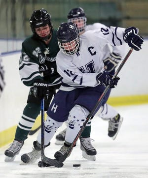 Hudson's Sullivan Clark, right, maintains possession of the puck against Strongsville's Ethan Warner during the first period of a hockey game, Wednesday, Feb. 10, 2021, in Cleveland, Ohio. [Jeff Lange/Beacon Journal]