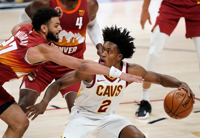 Cleveland Cavaliers guard Collin Sexton, right, drives the lane as Denver Nuggets guard Jamal Murray defends in the second half of an NBA basketball game Wednesday, Feb. 10, 2021, in Denver. (AP Photo/David Zalubowski)