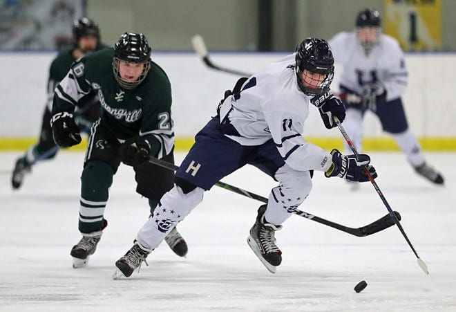 Hudson's Ty Koerbel, right, cuts across the ice ahead of Strongsville's Nolan Marcum during the first period of the Explorers' 6-0 Baron Cup win Wednesday night. [Jeff Lange/Beacon Journal]