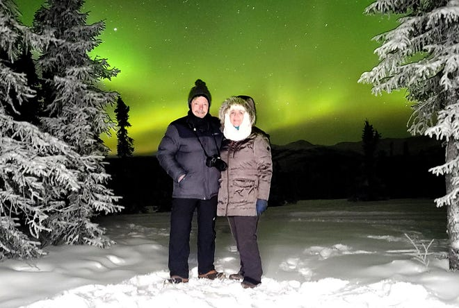 Mike and Kathy Haynes pose in front of a green sky in Alaska this month as the northern lights performed behind them.