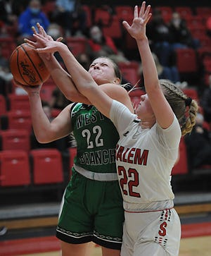 West Branch's Sydney Mercer drives to the basket against Salem's Alivia Davidson-Chuck in an Eastern Buckeye Conference game at Salem High School Wednesday, February 10, 2021.