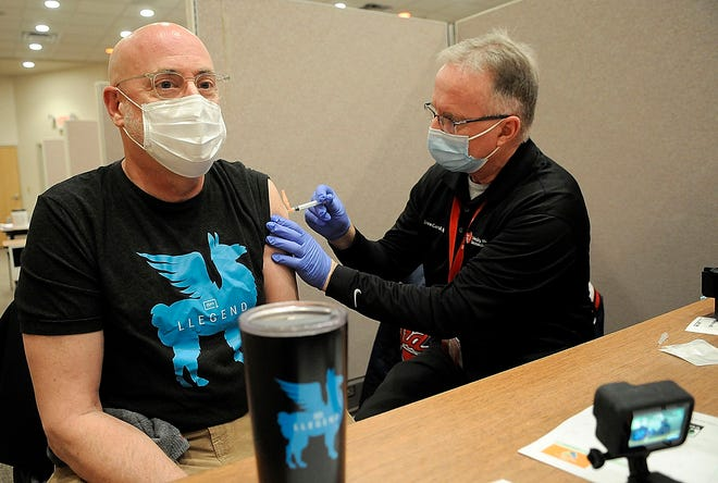 Tom Roepke gets his second dose of the COVID-19 vaccination from University Hospitals Samaritan Medical Center's Steve Carroll at the Ashland County Health Department's clinic last week. The department is scheduling appointments based on age tiers. TOM E. PUSKAR/TIMES-GAZETTE.COM