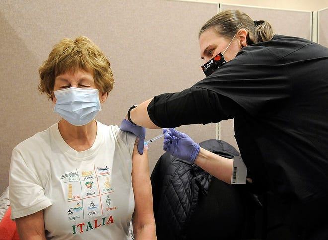 Mary Henikman gets her COVID-19 vaccination from Missy Repp, a nurse from the Inn at Ashland Woods, at the Ashland County Health Department's clinic Thursday, Feb. 11, 2021 at University Hospitals Samaritan on Main. Ashland County had vaccinated over 7% of its population as of Thursday. TOM E. PUSKAR/TIMES-GAZETTE.COM