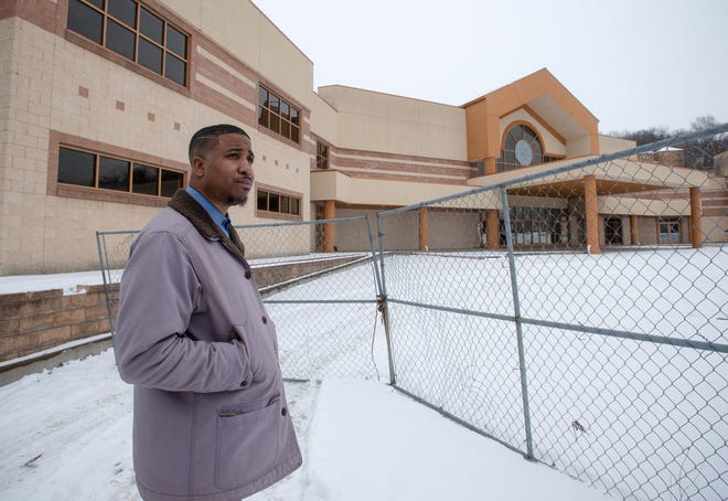 Zabriawn Smith stands in front of the building on the corner of Sixth Avenue and Washington Street that is currently owned by Sound the Alarm Ministries. The Aliquippa building has remained unfinished for nearly 16 years. Smith, a Realtor, is attempting to take over the building through his nonprofit, Aliquippa Green.