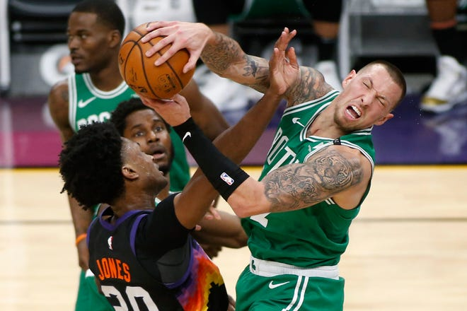 Boston Celtics forward Daniel Theis, right, is fouled by Phoenix Suns center Damian Jones, left, as he grabs a rebound during Sunday's game in Phoenix.