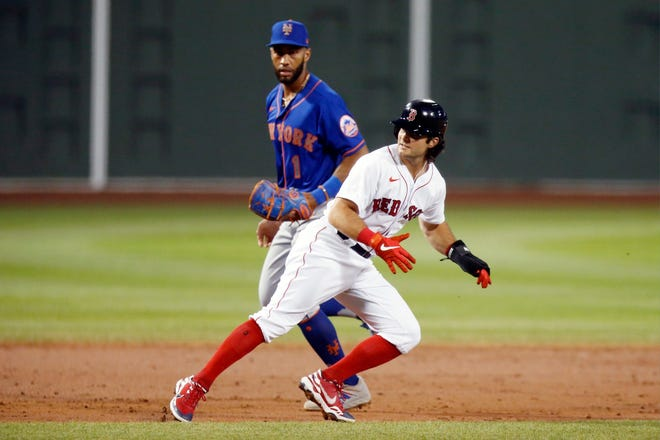 Boston Red Sox's Andrew Benintendi, right, reverses course during a July 28 game against the New York Mets in Boston. The Red Sox completed a three-team deal with the Mets and Kansas City Royals on Wednesday night that sent Benintendi to the Royals in exchange for Franchy Cordero, pitcher Josh Winckowski and three players to be named later.
