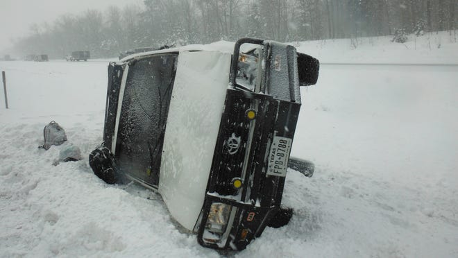 The two occupants of this truck received minor injuries in the rollover accident on I-75 caused by slippery roads Monday morning.