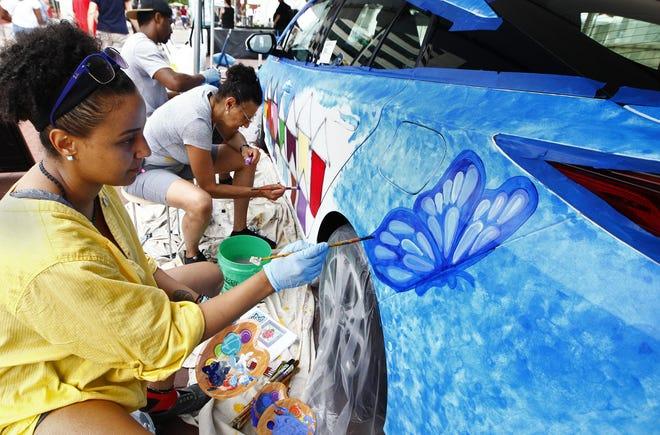 Shelbi T. Harris-Roseboro, left, paints a 2020 Toyota Prius Prime at the 2019 Columbus Arts Festival Downtown.