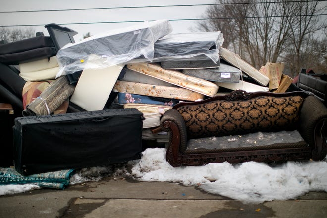 Mattresses, couches, and bed frames, some still covered in plastic, are shown piled up Feb. 8 outside Whispering Oaks apartment complex, where refugee families were evicted so renovation work could be performed. Many of them were given 30 days notice to get out.
