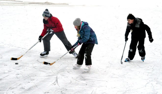 Cameron, Maddison, and Austin Kraft play a little hockey on the frozen rink at Hilltop Park in Orrville.