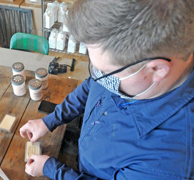 Sterling Candle Co. owner Adam Hanzie places a label on the candle.