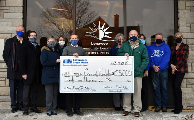 Representatives from TLC Community Credit Union, the Lenawee Community Foundation and the Kiwanis Regional Trail Authority display a check for $25,000 that was presented to the foundation and the trail authority by TLC. Pictured, from left, are TLC senior vice president of administration Jeff Brehmer, TLC assistant vice president and Tecumseh branch manager Sean Armstrong, TLC vice president of marketing Suzanne Miller, Tecumseh City Council member and Tecumseh Area Chamber of Commerce executive director Vicki Riddle, Lenawee Community Foundation president and CEO Joe Williams, Tecumseh City Council member Stephanie Harmon, TLC president and CEO Randy Smith, Lenawee Community Foundation community outreach and office manager Janie Colton, Tecumseh City Council member Austin See, and Lenawee Community Foundation project mnager Cynthia Heady.