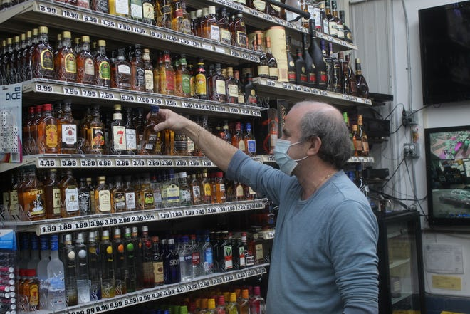 Tim Ward, manager of Super Liquor III, 800 S. Main St., Adrian, grabs a bottle of Canadian Mist whiskey from behind the counter on Wednesday. Super Liquor, like most local liquor stores, enjoyed an increase in sales last year.