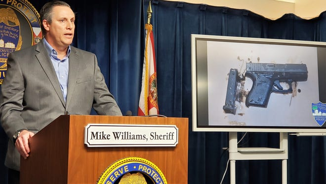Sheriff's Office Director Mike Bruno announces the arrests of four boys as one of the guns stolen and recovered from the Westside gun store is shown.