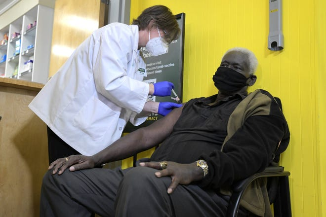 Robert Tillman gets his first dose of the COVID-19 vaccine from pharmacist Sherry Daughtry at the Harveys Supermarket  in downtown Jacksonville Thursday. The store received 100 of the 8,100 doses distributed to its parent company, Southeastern Grocers.