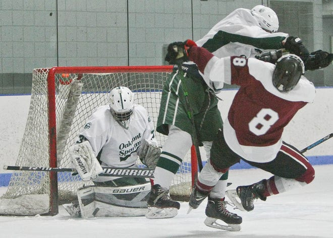 Oakmont goaltender Cathal Wells makes a save as Spartans defender Ben Mattson delivers a hit on Fitchburg/Monty Tech's Cooper Hall during Wednesday evening's game at Veterans Arena in Gardner. The visiting Red Raiders won 6-2.