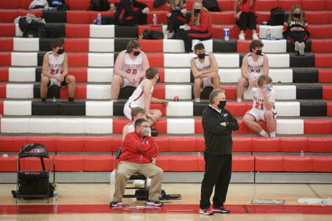 As bench players socially distance themselves in the bleachers, United High School boys basketball coach Doug Dennison, standing, and assistant Jeff Hannam watch the action on the court during Wednesday night's 71-46 win over visiting Knoxville in rural Monmouth.