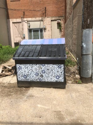 A decorated dumpster sets in an alley in downtown Denison. The city council is expected to consider an ordinance that would tighten restrictions against dumpster diving.