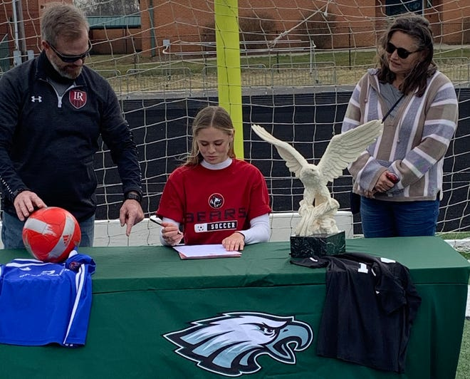 With her parents, Brian and Jennifer, watching, East Henderson soccer standout Aubrie Pressley signs with Lenoir-Rhyne Universtiy last month at East.