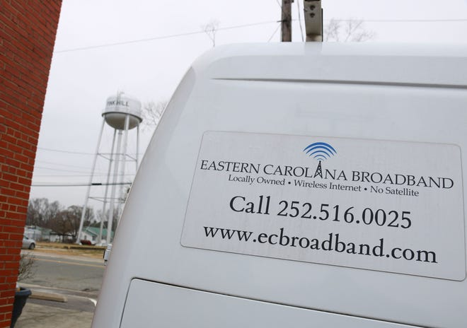 An Eastern Carolina Broadband service van sits outside the wireless internet company in the Town of Pink Hill Thursday, Feb. 11, with the town's water tower in the background.