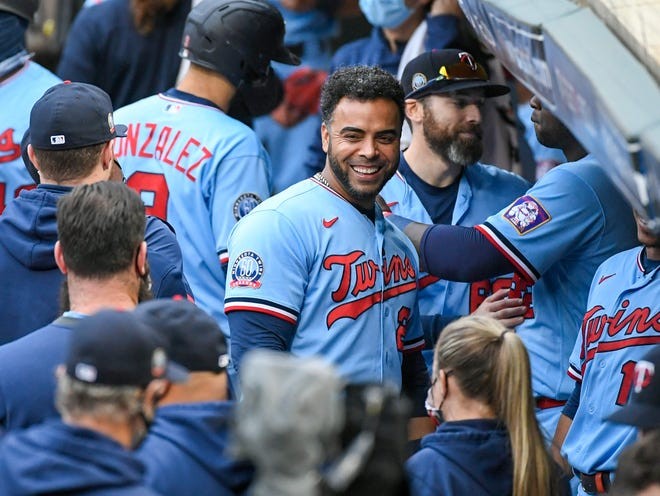 FILE - In this Sept. 27, 2020, file photo, Minnesota Twins' Nelson Cruz, center, smiles in the dugout after the Twins clinched the AL Central championship with the Chicago White Sox's loss during the tenth inning of a baseball game in Minneapolis.
