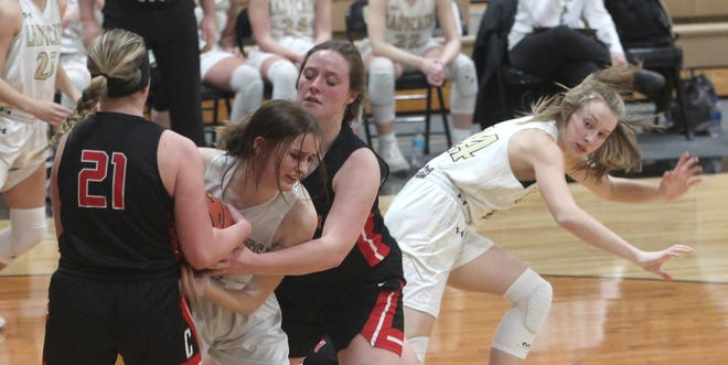 Cairo freshman Jersey Bailey gets sandwiched between a pair of Community R-VI players Wednesday night as she fights to gain control of a rebound while teammate Morgan Taylor stumbles while moving forward. Cairo girls lost 61-43 at home to the Lady Trojans.