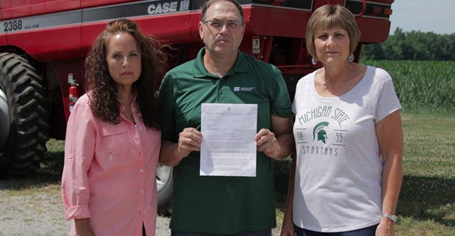 Zell Eisenmann holds arejection letter his family received from the Michigan Occupational Safety and Health Administration concerning an appeal they filed to paying a $12,000 fine for the accidental death of Zell's brother, Keith,  in a fall in 2019. Standing next to Zell are Barb Eisenmann, right, Keith's wife, and Zell's wife, Rita.