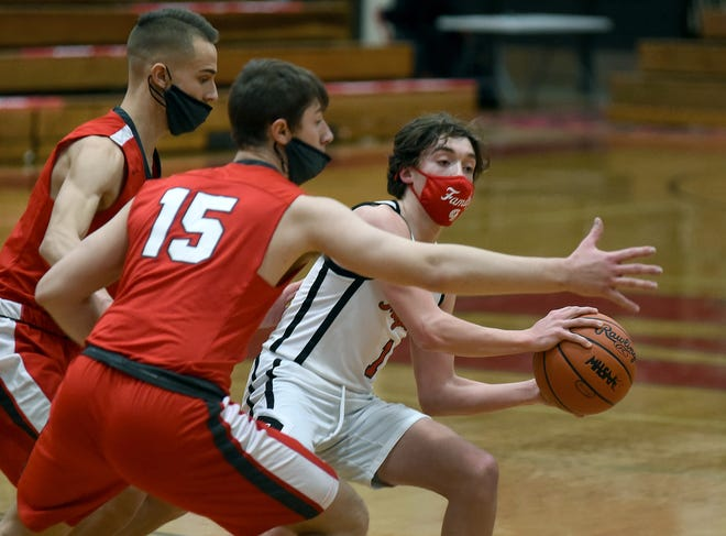 Gabe Sweat of Monroe attempts to pass around Bedford defenders Tyler Krupp and Brandon Nigh (15) Wednesday night. Nigh scored 19 points in a 54-50 Mule victory. [MONROE NEWS PHOTO BY TOM HAWLEY]
