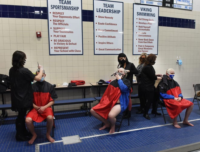 A tradition for Dundee High School, hair stylist Heather Hay, Kortney Griffith, Kristine Liedel and owner Heather Lomazzo of Rootz Hair Salon in Dundee bleached the hair of swimmers Drew Eastman, Connor Moran and Cole Cousino this week as they prepared for the Monroe County swim meet at Dundee High School Saturday. Fifteen of the twenty swimmers/divers carried on this tradition. [MONROE NEWS PHOTOS BY TOM HAWLEY]