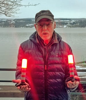 Greg Talomie shows two LED flares lit, as he stands by Canandaigua Lake outside his lake home in Gorham.