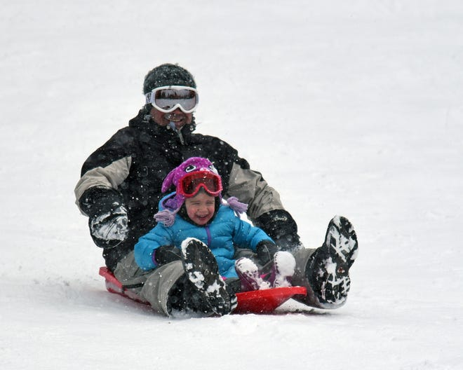 A father and daughter enjoy sledding at Snowman's Hill on Highway 89 between Mount Shasta and McCloud in February of 2017.