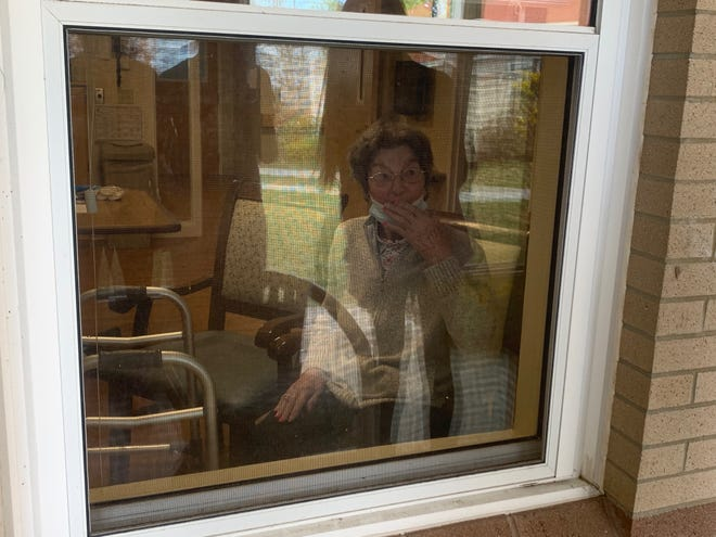 Genoveffa Lambert, a resident of St. Ann Rehabilitation in Dover, greets visitors during a window visit.